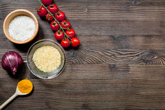 Rice, spices and vegetables for paella wooden desk background top view space for text Royalty Free Stock Images
