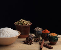 Rice and spices on the wooden board Stock Photos