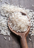 Rice in spoon. Rice in wooden spoon on old plank Stock Photo