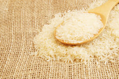 Rice with spoon on jute background Stock Images
