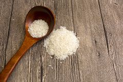 Rice, a staple of the world. Uncooked white rice in a wooden spoon. Stock Photos