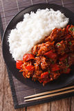 Rice with stewed pork in sweet and sour sauce closeup. Vertical Stock Photo