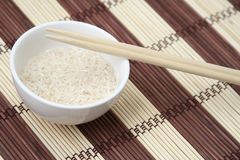 Rice and sticks. White bowl of rice and chinese chopsticks, on bamboo background, view from above Royalty Free Stock Images