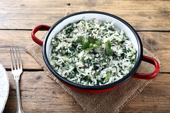 Rice with stinging nettles. On kitchen rustic table background royalty free stock photo
