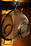 Rice strainer. A rice and pasta strainer hanging with  sunlight falling on it Royalty Free Stock Photo