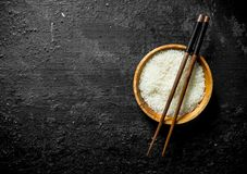 Rice for sushi in a wooden plate with sticks. On black rustic background stock images