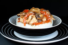 Rice topped with chicken, vegetables and Shitaki. Rice with stir fry chiken and vegetables over black background Royalty Free Stock Photos