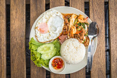 Rice topped with stir-fried combination. Rice topped with stir-fried combination of pork, chicken, squid, shrimp, basil and fried egg. Thai food Stock Photo