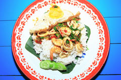 Rice topped with stir-fried seafoods and basil with Fried egg in the big tray, Thai Language is Kao Pad Kaprao Talay. As thai foods background or print card Royalty Free Stock Photos
