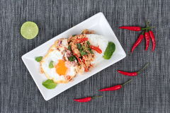 Rice topped with stirred  minced-pork ,squid ,basil and fried egg(sunny up) on black napery. Stock Photo