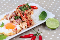 Rice topped with stirred  minced-pork ,squid ,basil and fried egg(sunny up) on brown napery. Selective focus. Royalty Free Stock Image