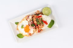 Rice topped with stirred  minced-pork ,squid ,basil and fried egg(sunny up) on white background. Stock Photography