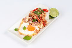 Rice topped with stirred  minced-pork ,squid ,basil and fried egg(sunny up) on white background. Stock Photo