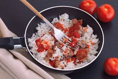 Rice with turkey minced meat and organic tomato sauce in frying pan royalty free stock photo