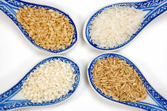 Rice varieties. A selection of rice varieties in blue spoons isolated on white background Royalty Free Stock Photography