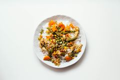 Rice with vegetables: carrots and corn, green beans, peas with pumpkin seeds and spices on white background. top view Stock Photography