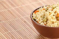 Rice with vegetables in a ceramic bowl on a mat bamboo Royalty Free Stock Photography