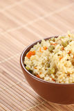 Rice with vegetables in a ceramic bowl on a mat Stock Image