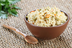 Rice with vegetables in a ceramic bowl on a mat Stock Photo