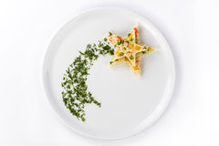Rice with vegetables laid out in the form of a star. Rice with vegetables on a white plate is laid out in the shape of a star with a plume of dill Stock Photo
