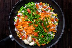 Rice with vegetables in a pan to cook. Rustic style. Stock Photo