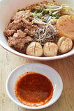 Rice vermicelli topping pork ball and meat in brown soup with chili sauce Royalty Free Stock Photo