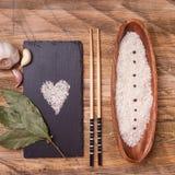 Rice w pucharze z czosnkiem i podpalanym liściem, odgórny widok Fotografia Stock