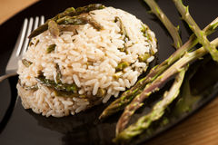 Rice with wild asparagus on a blavk plate with fork served on a Stock Photography