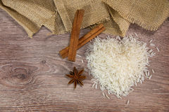 Rice on wood with cinnamon sticks. On wood background royalty free stock photo