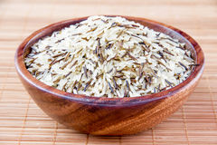 The rice in a wooden bowl. On bamboo Stock Photography