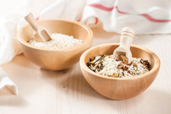 Rice in wooden bowl with ingredients for risotto. Mix of raw rice and dried vegetables in wooden bowls on a light background Stock Photography