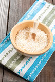 Rice in wooden bowl with ingredients for risotto. White rice and dried vegetables in wooden bowl on a light background Royalty Free Stock Photo