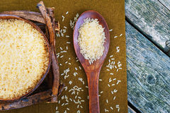 Rice in a wooden bowl and a wooden spoon Stock Photos