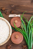 Rice in wooden plate and anise on brown wooden background. Rice and spices in ecological container. Set for cooking. Set for spa. Rice in wooden plate and anise Royalty Free Stock Photography
