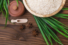 Rice in wooden plate and anise on brown wooden background. Rice and spices in ecological container. Set for cooking. Set for spa. Rice in wooden plate and anise Stock Images