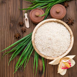 Rice in wooden plate and anise on brown wooden background. Rice and spices in ecological container. Set for cooking. Set for spa. Rice in wooden plate and anise Royalty Free Stock Photos