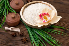Rice in wooden plate and anise on brown wooden background. Rice and spices in ecological container. Set for cooking. Set for spa. Rice in wooden plate and anise Stock Photography