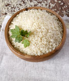 Rice on the wooden plate. Rice with herbs in a wooden plate on linen napkin Royalty Free Stock Image