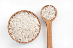 Rice in wooden spoon and bowl on white background. Royalty Free Stock Image