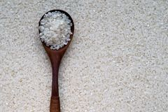Rice in a wooden spoon over. White Background, top view. texture of white round grain uncooked raw rice Stock Image