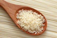 Rice in a wooden spoon on rice noodles background. Close-up Stock Photo