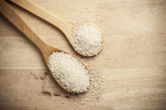 Rice on Wooden Spoons. And wood table Royalty Free Stock Photo