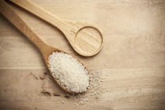 Rice on Wooden Spoons. And wood table Royalty Free Stock Image