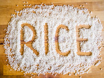 Rice word made of rice. On wooden board Royalty Free Stock Photo