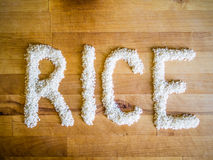 Rice word made of rice. On wooden board Royalty Free Stock Image