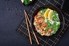 Rice with young green peas, shrimps and arugula in black bowl. royalty free stock image