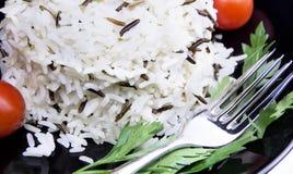 Rice z czereśniowymi pomidorami i zielenie na czarnym talerzu Obraz Royalty Free
