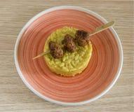 Rice z kapusty i wieprzowiny klopsikami na pomarańcze talerza drewnianym tle Zdjęcia Stock