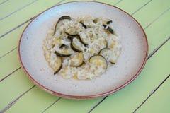 Rice z zucchini w nieociosanym naczyniu na zielonym drewnie Fotografia Royalty Free