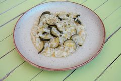 Rice with zucchini in a rustic dish on green wood royalty free stock photography